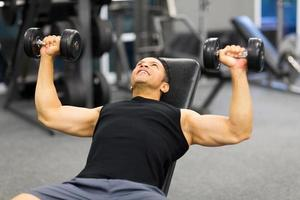Mann mittleren Alters, der Gewichte im Fitnessstudio hebt foto