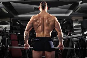 muskulöser Mann, der einige schwere Hanteln anhebt