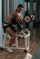 Macho Mann, der Gewichte mit Langhantel hebt foto