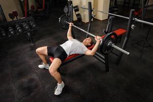 junger Mann, der Bankdrücken Übung im Fitnessstudio macht foto