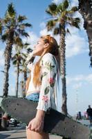 junge stilvolle Frau, die sich nach dem Reiten auf ihrem Longboard im Freien entspannt