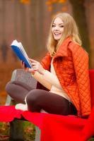 Mädchen, das im Herbstpark liest, das Buch liest foto