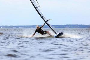 junger Mann, der den Wind in Wasserspritzern surft