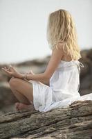 Frau, die Yoga am Strand praktiziert foto