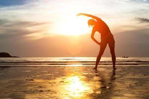 Schattenbildfrau, die Yoga am Strand bei Sonnenuntergang praktiziert. foto