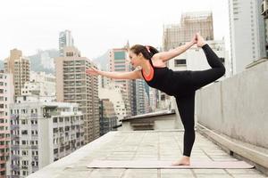 asiatisches Mädchen, das Yoga auf einem Dach in Hongkong macht foto