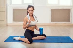 schöne sportliche sportliche Frau, die nach einigen auf Yogamatte sitzt foto