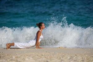 kaukasische Frau, die Yoga an der Küste praktiziert