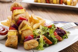 Gegrillte Hähnchen-Spieße mit Ananas, Paprika und Zwiebeln servieren