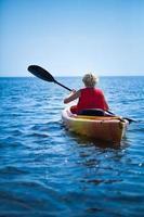 Frau, die eine Sicherheitsweste trägt, die allein zum Meer hinausgeht
