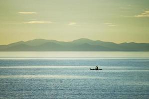Kajakfahrer in der Abenddämmerung, Südinsel im Hintergrund