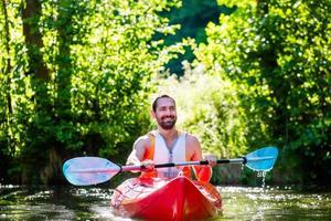 Mann, der mit Kajak auf Fluss für Wassersport paddelt