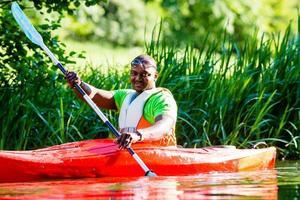 afrikanischer Mann, der mit Kanu auf Waldfluss paddelt