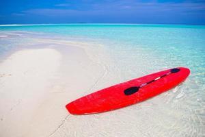 rotes Surfbrett am weißen Sandstrand mit türkisfarbenem Wasser foto