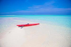 Surfbrett am weißen Sandstrand mit türkisfarbenem Wasser foto