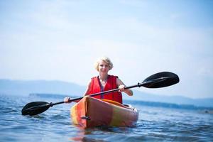 Frau mit Sicherheitsweste, die allein auf einer ruhigen See Kajak fährt