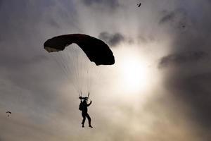 Fallschirmspringer-Silhouette gegen Himmel foto