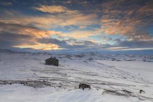 verschneite Landschaft mit altem Holzhaus