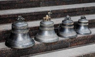 kleine Kirchenglocken stehen in einer Reihe foto
