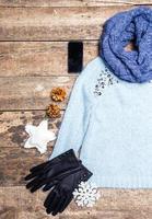 Winterkleidung auf hölzernem Hintergrund.