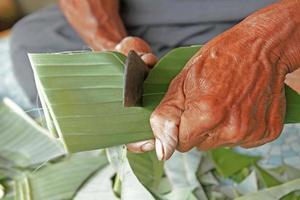 Hand des alten Mannes, der das Bananenblatt schneidet foto