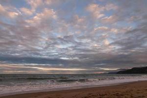 tropischer Strand im Winter mit dramatischen Wolken