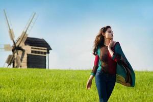 junges schönes Mädchen mit langen dunklen Haaren im grünen Feld foto