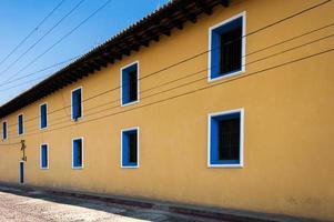 gelb gestrichenes Stadthaus mit blauen Fenstern
