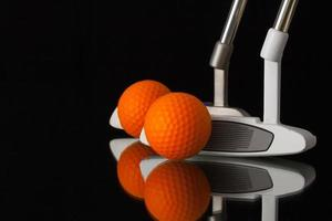zwei verschiedene Golfputter auf einem schwarzen Glasschreibtisch foto
