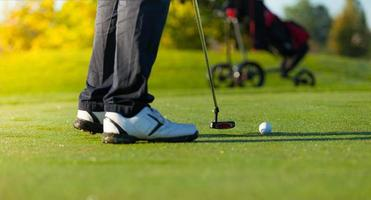 Nahaufnahme des Mannes, der Golf auf grünem Platz spielt foto
