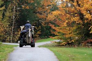 Golfspieler, der im Golfwagen in Richtung Putting Green reitet foto