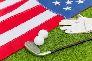 Golfausrüstung und eine amerikanische Flagge auf dem Rasen foto
