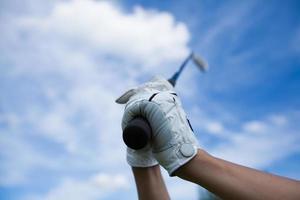 Golfhände in Handschuhen halten Eisen am Himmel foto