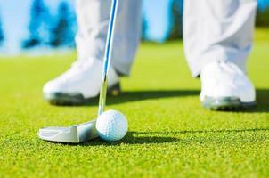 Detailfoto des Mannes, der Golfball in das Loch setzt foto