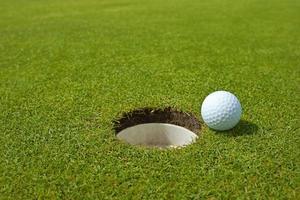 Golf, Ball auf dem Grün neben Loch liegen foto