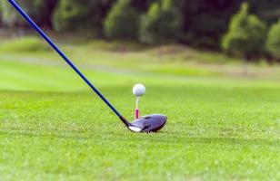Golfausrüstung, Golfball mit Abschlag auf Platz und Schläger foto