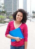 afroamerikanische Studentin, die in der Stadt steht foto