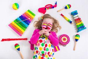 lustiges kleines Mädchen mit Musikinstrumenten
