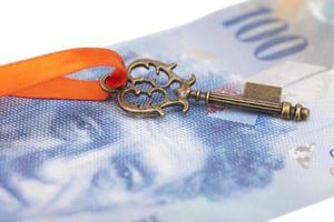 Schlüssel zum Erfolg mit roter Schleife auf Schweizer Franken