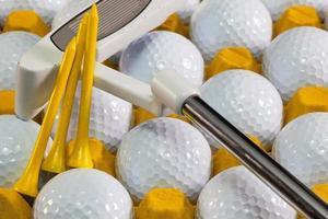 weiße Golfbälle in der gelben Box und Putter foto