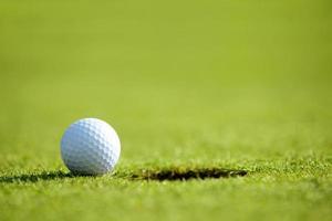 Golfball in der Nähe von Loch foto