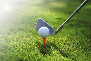 Golfschläger und Ball im Gras foto