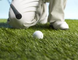 Golfspieler, der sich darauf vorbereitet, den Ball zu schlagen foto