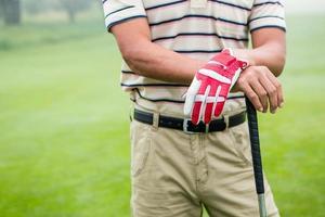 Golfer steht und stützt sich auf seinen Schläger foto