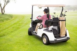 Golfer fährt in seinem Golfbuggy foto