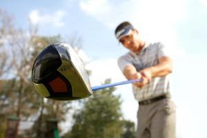 junger Mann, der Golf spielt, niedrige Winkelansicht foto