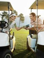 Golfer sitzen in Golfwagen mit Scorekarte foto
