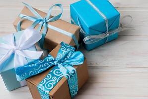 Schachteln mit Geschenken mit Bändern auf Holzrücken verziert foto