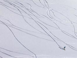 Snowboarder bergab auf Pistenhang mit Neuschnee foto