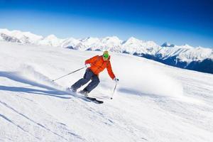 Skifahrer in Maske rutscht schnell beim Skifahren von der Piste